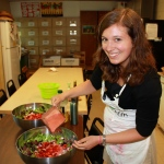 Our Marketing Assistant Rosalind pouring strawberry balsamic vinaigrette over strawberry greens salad